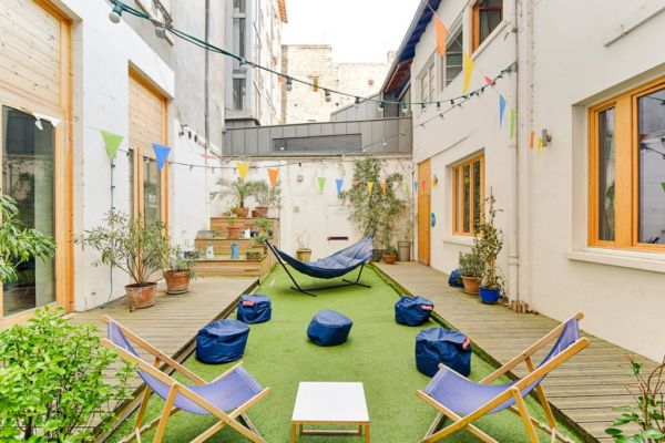 outdoor patio with beanbag chairs, a hammock and string lights