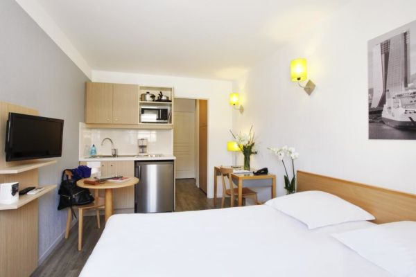 studio hotel room with bed and kitchenette