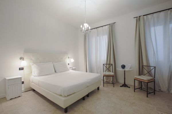 white hotel room with chandelier