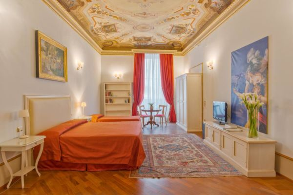 hotel room with red bed and frescoed ceiling