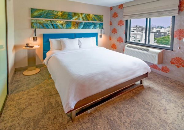 hotel room with wood floors and large white bed
