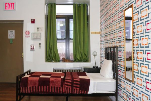 hostel room with patterned wall paper, twin bed and green curtains